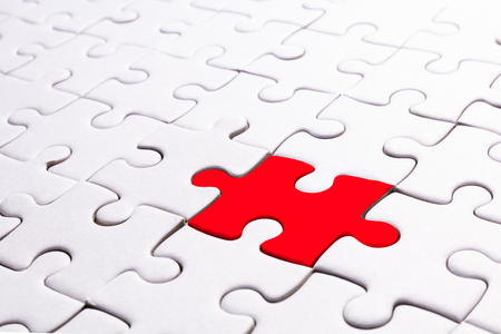 close up pattern of white jigsaw and one part is red for concept background Standard-Bild - 119600640