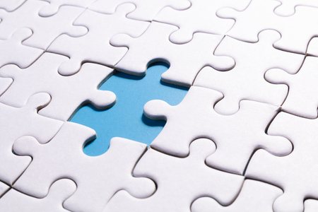 close up white jigsaw and missing one part of jigsaw on blue color background with concept