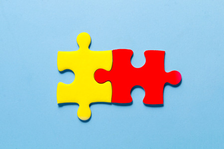 close up red and yellow color a part of jigsaw on blue color background with concept