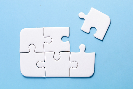 close up white color a part of jigsaw on blue color background and one part out of group with concept