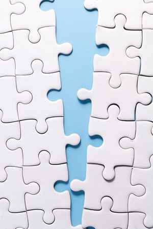 close up white jigsaw on blue color background with concept