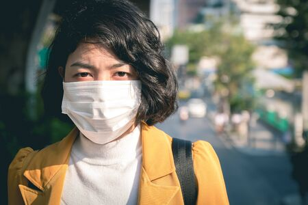 asian woman wearing face mask for protection air pollution in city