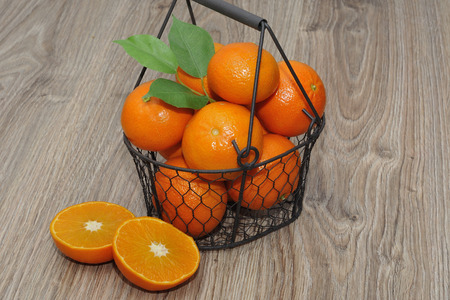 Clementines in a basket on a wooden table. Stock Photo