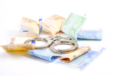 Handcuffs and money on a table Imagens