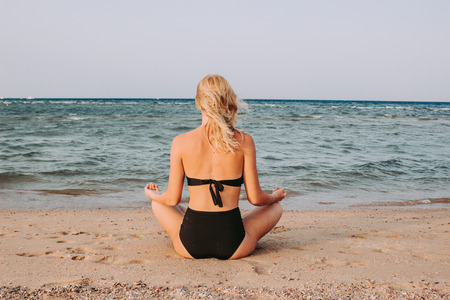 Young summer woman meditates on the sea sitting on the beach Stock fotó