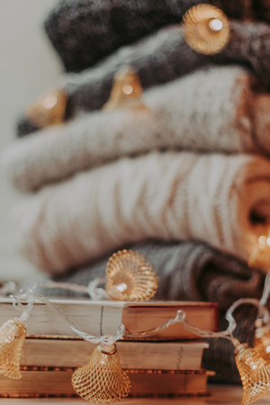 Home decor, sweaters, a stack of books and light bulbs, cozy winter interior details. Close-up - Image