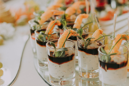 Delicious canapes at the event. Catering for a party. Snacks with cherry tomatoes, shrimps, cheese, grapes and spices in short glasses on a white served table.