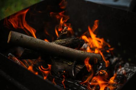 Rote Flamme aus einem Baumschnitt, dunkelgraue Kohlen in einem Metallbecken Brennholz, das in einem Kohlenbecken auf einer leuchtend gelben Flamme brennt. Feuerflammen, die sich auf das Kochen von Kebabs vorbereiten. Holzkohle Kohlenbecken
