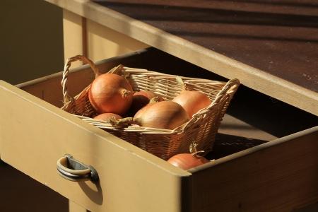 Zwiebeln in der Schublade eines antiken Küchentisches