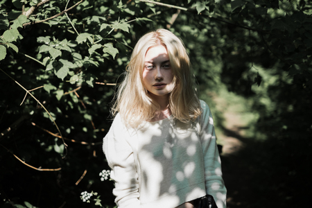 subtlety: portrait of a beautiful young blonde in the forest among the trees