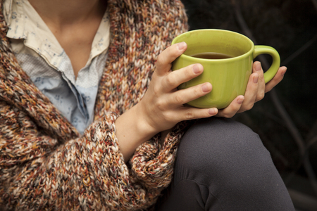 tea cosy: the womans hands are holding a green cup of tea. Russia.