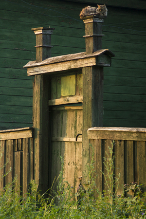 wicket: Wooden wicket and fence to the yard. cat sleeping on the gate. Stock Photo