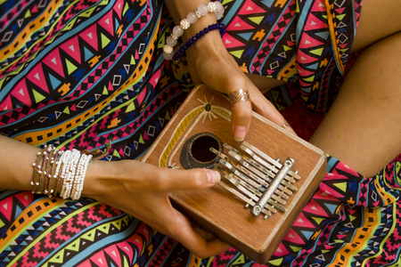 Woman holding kalimba in her hands and playing Reklamní fotografie