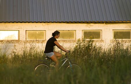 Nizhny Novgorod, Russia, August 05, 2016: a woman rides a bicycle past an old stable