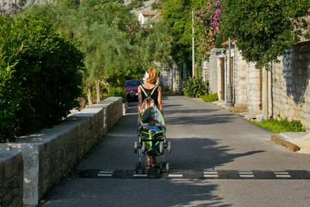 A woman with a backpack walking with a stroller in a resort town in Montenegro.