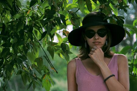 Portrait of a young woman in a hat and sunglasses.
