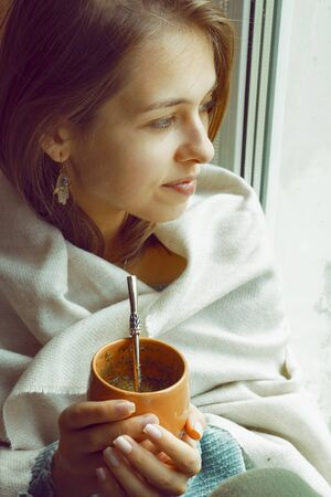 girl drinks mate on the windowsill by the window