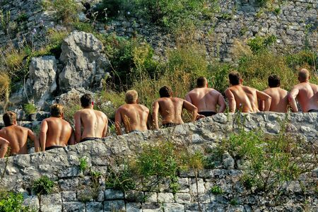 KOTOR, MONTENEGRO, September 26, 2016: A group of young men stopped to rest while climbing a fortress in Kotor.