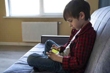 Focused boy enthusiastically plays in a smartphone.
