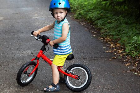 Toddler boy in bright clothes and helmet on balance bike
