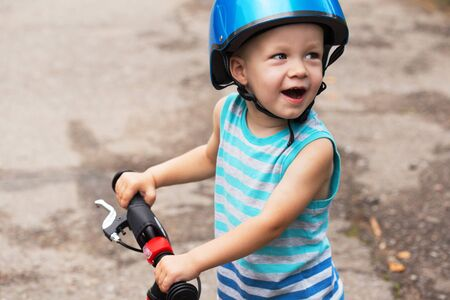 Happily smilling toddler boy in blue shirt and helmet standing on the road with balance bike.