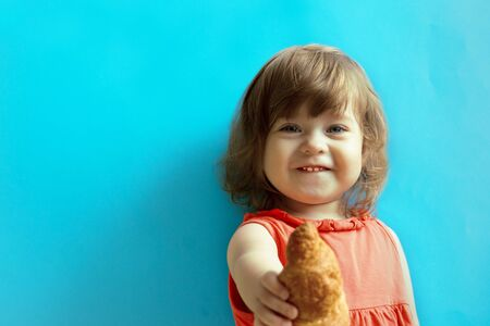 A little girl on a blue background looks at the camera and gives the viewer a croissant.