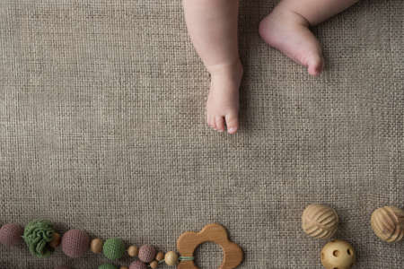 Flatlay with tiny chubby newborn baby legs and knitted and wood handmade toys