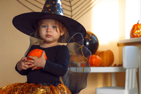 Portrait of a little girl in a witch costume with a pumpkin in her hands.