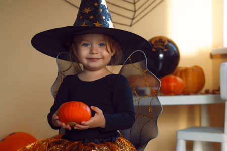 Portrait of a little smiling girl in a witch costume with a pumpkin in her hands.