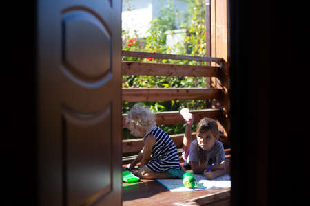 Two girls drawing on wooden veranda in the country house in sunny summer day. Cottagecore aesthetics concept. 스톡 콘텐츠