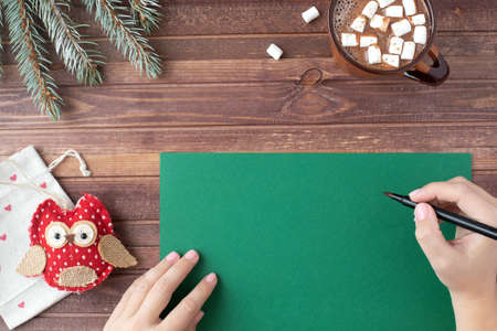 New year flat lay. Mockup with green paper, gift, female hands, christmas decoration and cocoa with marshmallow cup on brown wooden background. Winter holidays mood.