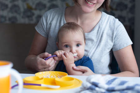 Cute infant trying to eat baby food using spoon and his cheerful mother assisting him. Yellow, blue and gray colors