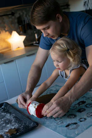 Young father and his small pretty daughter happily making Christmas ginger cookies together. Kitchen is decorated for New Year. Traditional family winter leisure activity Banco de Imagens