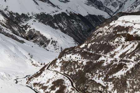 Road bends in the snowy mountains. Winter time. Monochrome. Gudauri, Georgia Banco de Imagens