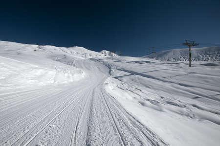 Recently prepared ski piste, ski lift and snowy mountains. Winter ski resort. Copy space. Gudauri, Georgia Banco de Imagens