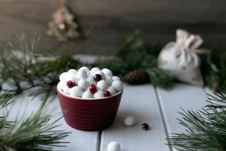 Sugared cranberries in red bowl with spruce branches and Christmas decoration. Traditional Russian New Year sweets. Winter holidays mood Banco de Imagens