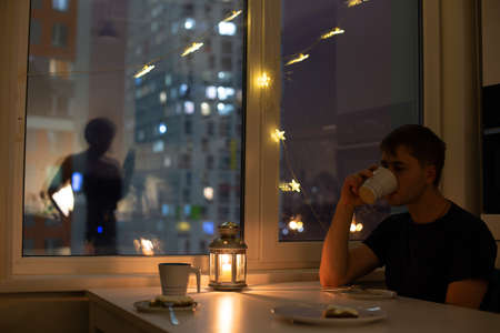 Female with mobile phone silhouette on the window, decorated for christmas and man having his dinner alone. Loneliness in the big city concept