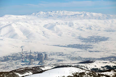 Snowy mountains picks and industrial town with smoking pipes. Nature pollution. Copy space Banco de Imagens