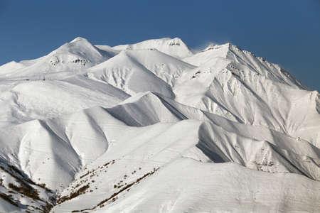 Snowy mountain picks in sunny weather. Winter ski resort. Copy space