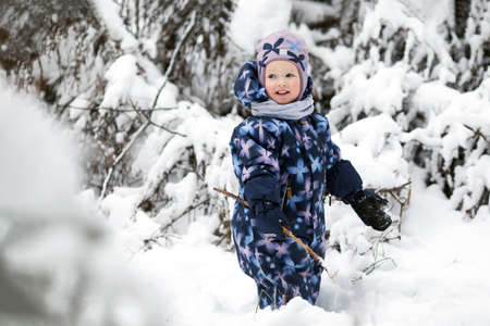 Cheerful smiling toddler girl wearing winter clothes having fun outside in snowy forest. Christmas and new year holidays