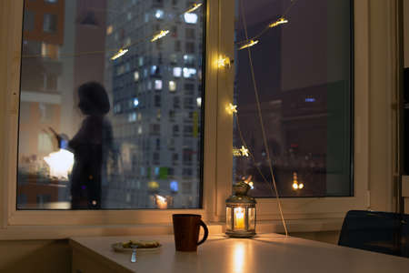Loneliness in the big city. Female with mobile phone silhouette on the window, decorated for christmas and dinner served for one person. Isolation and staying home concept Banco de Imagens