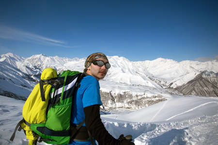 Man in bright sportive clothes and sun glasses with green backpack hiking in snowy mountains in Georgia. Copy space. Solo traveler and winter escape concept Banco de Imagens