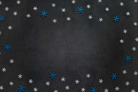 Dark Christmas and New Year background with cutted glitter silver and blue snowflakes. Frame with copy space