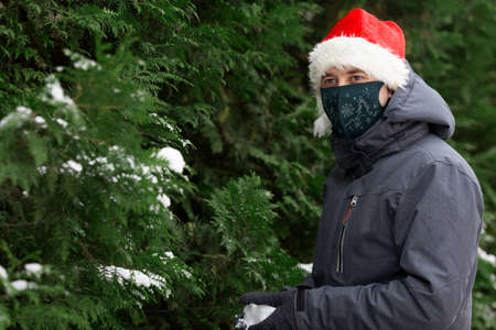Young man wearing ptotective face mask decorated for New Year and Santa hat having fun outside in snowy winter day. Christmas eve. Man is playing with snow. Holidays and Covid-19 health care concept