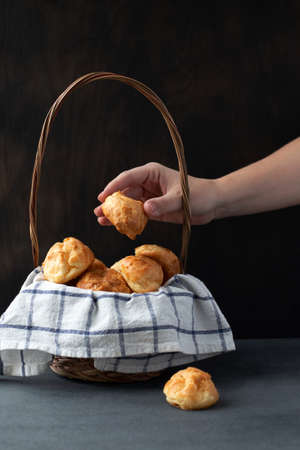 Basket with Traditional French Gougeres - savory cheese pastry and female hand taking one of the buns on dark background