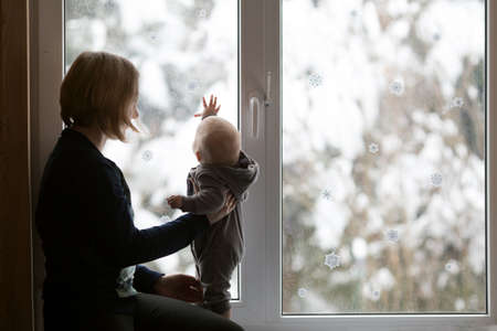 Young woman and her small child sitting on the window sill. Window is decorated for New Year. Snowy forest is outside. Christmas eve and family time concept Banco de Imagens
