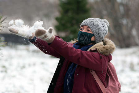 Young woman wearing ptotective face mask decorated for New Year and winter clothes having fun outside in snowy day. Christmas eve. Woman is playing with snow. Holidays and Covid-19 health care concept
