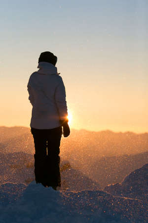 Female silhouette high in the mountains. Winter, sunrise. Weather is windy and snowy. Early morning on the top