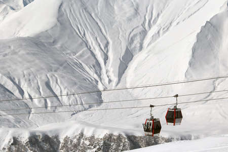 Ski lift cabins and snowy mountains. Winter ski resort. Copy space
