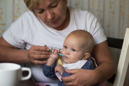 Grandmother feeding her small grandchild. Baby food, taking care and generation link concept